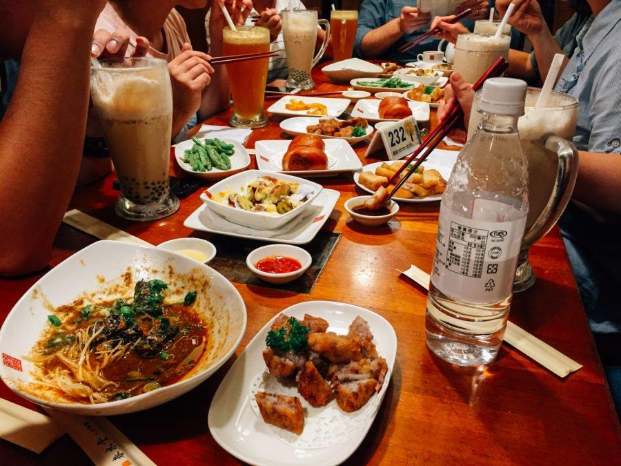 Nguyên bàn đầy món ăn và các ly trà khổng lồ
